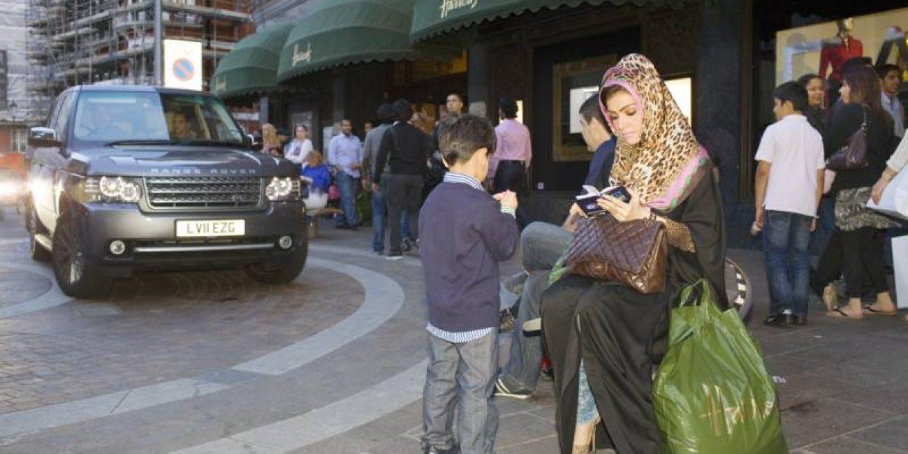 Een Arabische vrouw op een bankje voor het Londense warenhuis Harrods